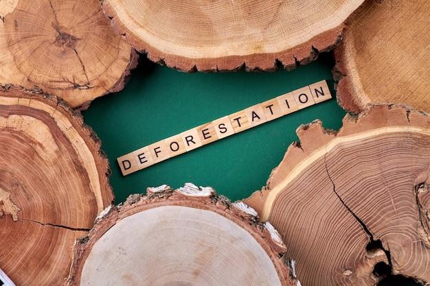 垂直ショットの森林破壊の概念。緑の背景に木製のスライス。