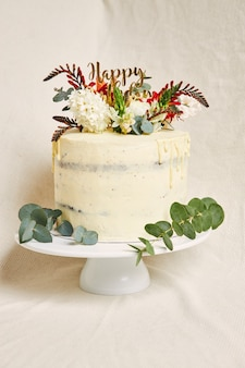 Vertical shot of a delicious birthday white cream flowers on the top cake with a drip on the side