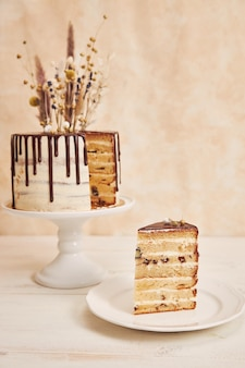 Vertical shot of delicious boho cake with chocolate drip and flowers on top with golden decorations