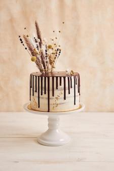 Colpo verticale della deliziosa torta boho con gocce di cioccolato e fiori in cima con decorazioni dorate