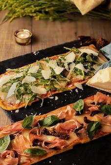 Colpo verticale di delizioso pane ripieno di pancetta, verdure e formaggio su un tavolo di legno