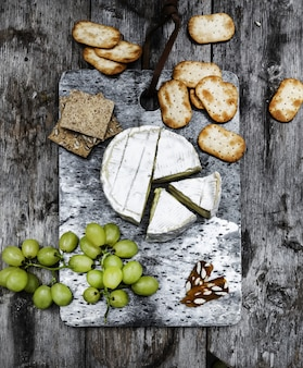 Vertical shot of delicious brie cheese on a wooden deck