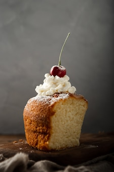 Vertical shot of a delicious cake with cream, powdered sugar, and a cherry on top