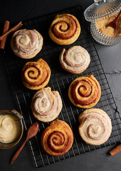 Vertical shot of delicious cinnamon rolls with a small bowl of white glaze on a black table