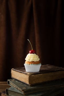 Vertical shot of a delicious cupcake with cream and cherry on top on books