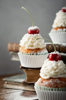 Vertical shot of delicious cupcakes with cream, powdered sugar, and a cherry on top on books