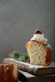 Colpo verticale di delizioso dessert con panna, zucchero a velo e ciliegina sulla torta sui libri