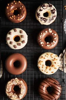 Vertical shot of delicious donuts covered in the white and brown chocolate glaze on a black table