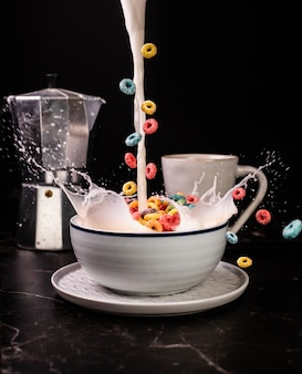 Vertical shot of delicious fruit loops in a bowl full of milk with a cup of coffee on a table
