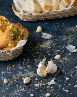 Colpo verticale di delizioso pane all'aglio e spicchi d'aglio con spezie sul tavolo