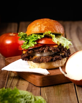 Vertical shot of a delicious hamburger on a wooden plate with a black background
