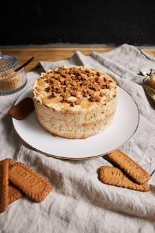 Colpo verticale di una deliziosa torta biscotto di loto con caramello con i biscotti sul tavolo