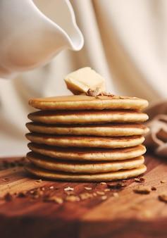 Colpo verticale di deliziose frittelle con burro, fichi e noci tostate su un piatto di legno