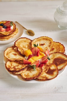 Vertical shot of delicious pancakes with fruits in the middle