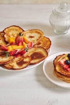 Colpo verticale di deliziose frittelle con frutta nel mezzo