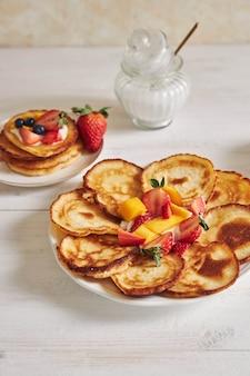 Colpo verticale di deliziose frittelle con frutta su un tavolo di legno bianco