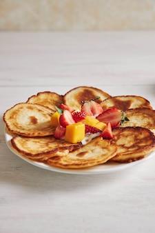Colpo verticale di deliziose frittelle con frutta sul tavolo di legno bianco
