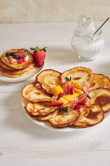 Colpo verticale di deliziose frittelle con frutta
