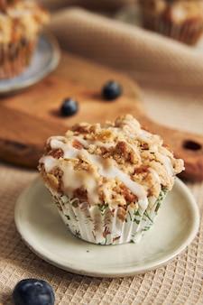 Ripresa verticale di deliziosi muffin vegani ai mirtilli su un tavolo decorato