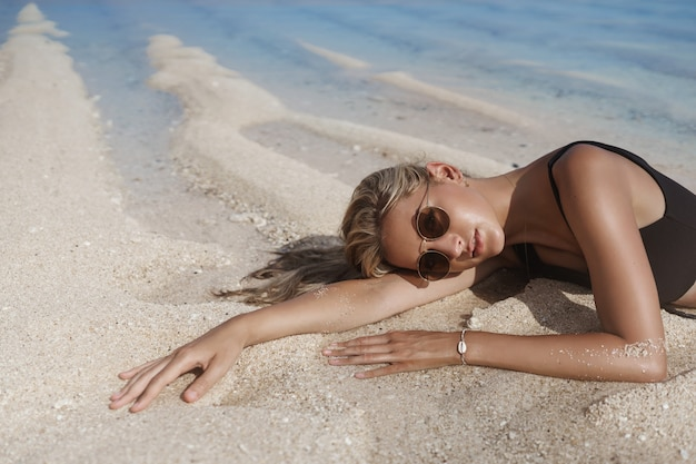 Vertical shot delighted carefree young blond woman wearing sunglasses and black bikini, lies on sandy beach.