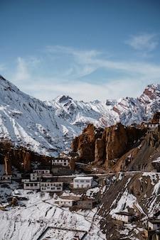 Colpo verticale di un monastero di dhankar nella valle di spiti con montagne innevate in