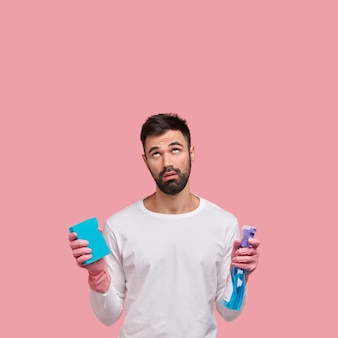 Vertical shot of displeased unshaven man focused above with tired expression, notices dirty ceiling in kitchen, wears rubber gloves for cleaning