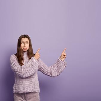Colpo verticale del labbro inferiore delle borse femminili dai capelli scuri insoddisfatte, arrabbiato con qualcosa di brutto, indossa un maglione lavorato a maglia, isolato su un muro viola con spazio libero per i tuoi contenuti promozionali.