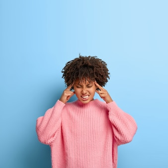 Vertical shot of dissatisfied woman with an afro posing in a pink sweater