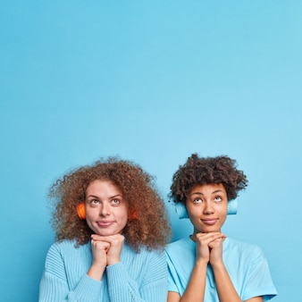 Vertical shot of diverse women with curly hair keep hands under chin focused above with thoughtful expressions stand next to each other isolated over blue wall copy space for your information