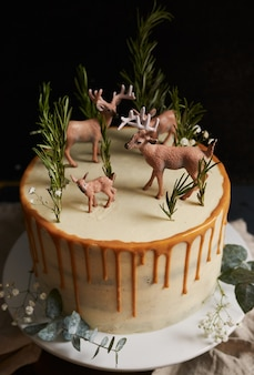 Vertical shot of a dreamy cake with white cream and orange drip with a forest and reindeers on top