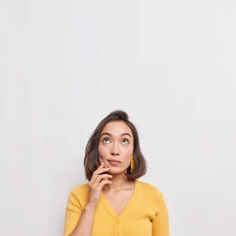 Vertical shot of dreamy thoughtful young asian woman with dark hair focused above considers something wears casual yellow jumper isolated over white wall copy space for your advertisement