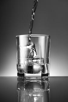 Colpo verticale di una bevanda che viene versata in un bicchiere con ghiaccio