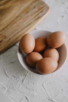 Vertical shot of eggs in a bowl next to a chopping board on the table