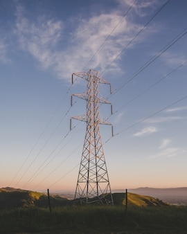 Vertical shot of an electric tower on a grassy field under a blue sky