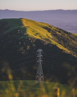 Vertical shot of an electric tower on a grassy mountain
