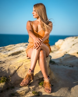Vertical shot of an elegant blonde female posing while sitting on the rock in the beach