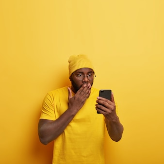 Vertical shot of embarrassed handsome guy with glasses posing with his phone