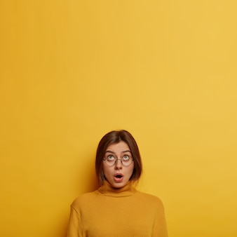 Vertical shot of emotional european woman concentrated above, gasps from fear and shock, reveals big secret, wears yellow turtleneck