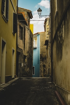 Vertical shot of an empty alley aligned with old yellow buildings leading to a blue building