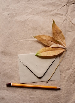 Vertical shot of an envelope with a dry maple leaf and a pencil