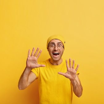 Vertical shot of excited attractive man reacts on something awesome, gestures and shows palms