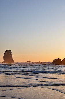 Vertical shot of the famous haystack rock on the rocky shoreline of the pacific ocean