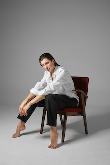 Vertical shot of fashionable attractive young brunette businesswoman wearing white shirt and trousers sitting barefooted in comfortable chair in relaxed posture, having rest after hard work