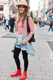 Colpo verticale di vagabondo femminile alla moda passeggia fuori per le strade, indossa un cappello alla moda, maglione a righe