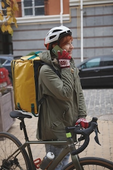Vertical shot of a female bicycle courier wearing delivery backpack