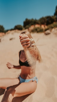 Vertical shot of a female in a bikini posing with sand on the beach