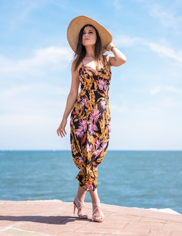 Vertical shot of a female in floral dress and hat captured by the ocean in san sebastian, spain