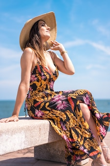 Vertical shot of a female in a floral sundress and a hat sitting by the sea captured in spain