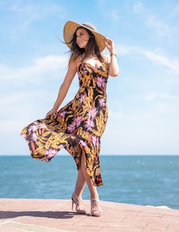 Vertical shot of a female in a floral sundress and a hat standing by the sea captured in spain