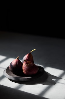 Vertical shot of figs in a wooden plate with sun rays falling on them with a blurred